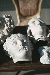 Close up. White plaster heads and  faces of statues, interior details from the Renaissance era on a wooden table at the European vintage market in Florence, Tuscany, Italy. Antiques and art objects