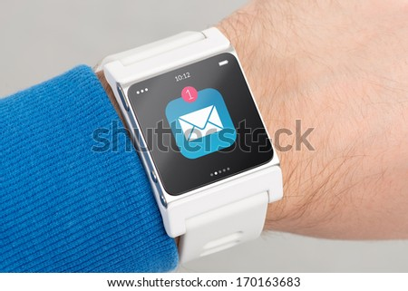 Close up white smart watch with unread message icon on the screen is on hand