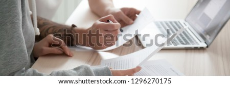 Close up wife husband hands, couple sitting at desk hold papers reading document received letter from bank use pc online banking, check planning family budget concept, banner for website header design