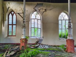 CLOSE UP: Windows are broken and facade decays inside an abandoned Catholic church. Exotic greenery grows over the ground and up rusty pillars inside a historic decrepit Christian chapel in Barbados.