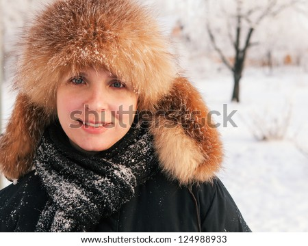 Close-up winter portrait of young smiling woman in fur hat