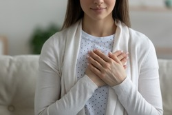Close up wishful peaceful young woman holding hands on chest, making wish, grateful sincere girl thanking fate, meditating, praying, sitting on couch at home, showing gratitude sign