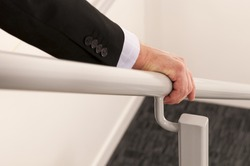 close up with selective focus of a business man's hand holding a hand rail while descending the stairs