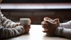 Close up woman and man sitting in cafe, holding warm cups of coffee on table, young couple spending weekend in cozy coffeehouse together, romantic date concept, visitors drinking hot beverages