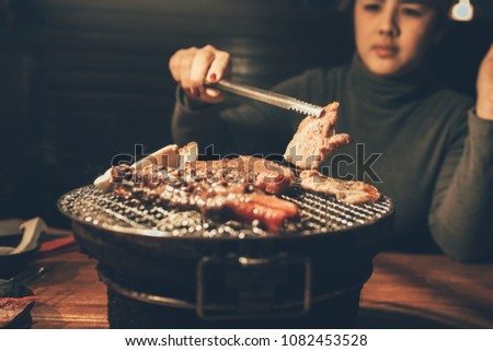 Close up woman cooking pork meat on a charcoal grill in restaurant.