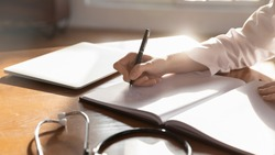 Close up woman doctor therapist writing in medical journal, sitting at table with stethoscope in office, working with documents, physician writing illness history, prescription in patient card