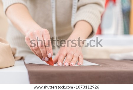 Close up woman draws with soap markup patterns on  fabric #1073112926