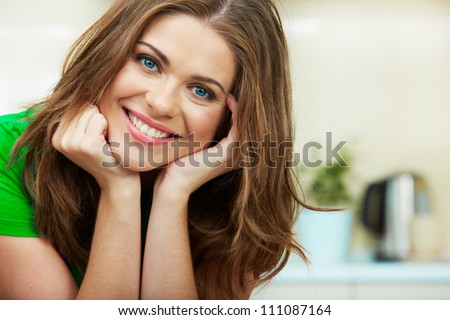 Close up woman face against home kitchen background. Clothes of green color. Portrait of smiling female model. #111087164