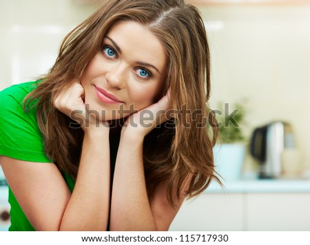 Close up woman face against home kitchen background. Clothes of green color. Portrait of smiling female model. - stock photo