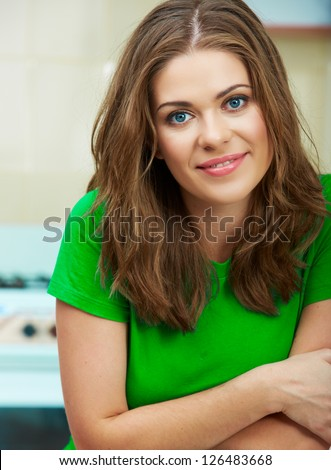 Close up woman face against home kitchen background. Clothes of green color. Portrait of smiling female model.