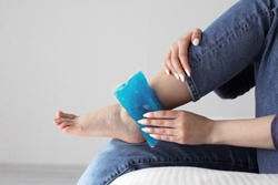 Close up woman feet and legs, and hands holding ice gel pack as cold compress on ankle due to stretching or injury, sitting on bed in apartment indoors