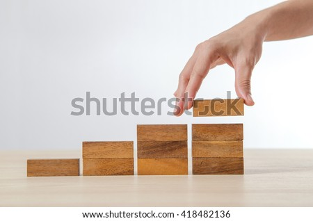 Close up Woman hand arranging wood block stacking as step stair. Business concept growth success process. #418482136