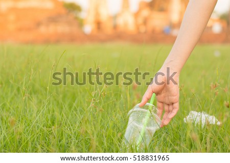 Close up woman hand Garbage collection in the park ,Hand of a woman throwing away a plastic bottle