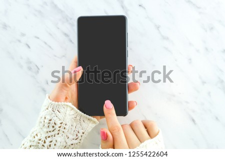 Close up woman hand holding black phone. Finger touches the touchscreen. Smartphone mockup. Flat lay. Top veiw. #1255422604