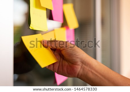 Close up woman hand holding colorful note sticky for brainstorm and share idea strategy workshop business.Brainstorming concept. #1464578330