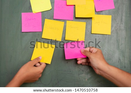 Close up woman hand holding colorful note sticky for brainstorm and share idea strategy workshop business.Brainstorming concept.