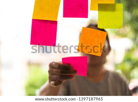 Close up woman hand holding note sticky for brainstorm ans share idea strategy workshop business.Brainstorming concept. #1397187965