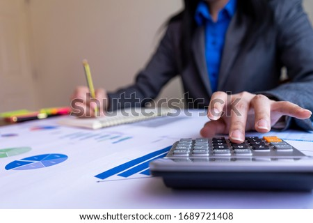 Close up woman hand using calculator and writing make note with calculate about cost at office.