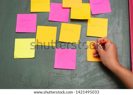 Close up woman hand writing colorful note sticky for brainstorm and share idea strategy workshop business.Brainstorming concept. #1421495033