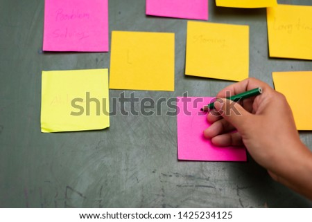 Close up woman hand writing colorful note sticky for brainstorm and share idea strategy workshop business.Brainstorming concept. #1425234125