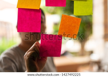 Close up woman hand writing colorful note sticky for brainstorm and share idea strategy workshop business.Brainstorming concept. #1427492225