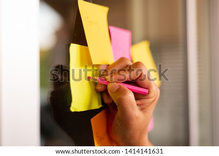 Close up woman hand writing note sticky for brainstorm and share idea strategy workshop business.Brainstorming concept. #1414141631