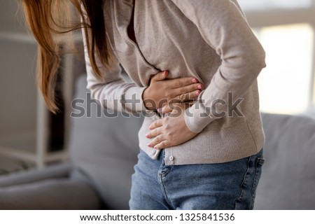 Close up woman holding belly, feeling discomfort, health problem concept, unhappy girl standing at home, suffering from stomachache, food poisoning, gastritis, abdominal pain, menstrual period