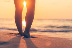Close up woman legs walking on tropical sunset beach with smooth wave and bokeh sun light wave abstract background. Travel vacation and freedom feel good concept. Vintage tone filter color style.