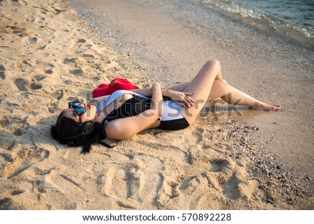 Close-up woman listening to music with headphones on the beach. Lady relax during summer vacation.Sexy body. Happy holidays.Background teenager beautiful sea.