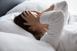 Close up woman lying in bed woke up in early morning touch head with palms feels tired not enough of rest, insomnia sleep disorder anxious by personal problems, unhealthy migraine and headache concept