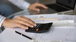 Close up woman managing planning budget, checking domestic bills, using calculator, sitting at table with financial documents and receipts, bookkeeper doing paperwork, calculating company expenses