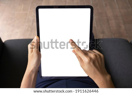 Close-up woman of hand held with digital tablet white screen on sofa in the living room. Concept of technology, connection, communication. Stockfoto ©