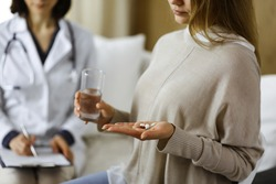 Close-up woman-patient holding pills near her doctor, time to take medications, cure for headache or remedy pain killer drugs. Stay at home concept during Coronavirus pandemic and self isolation