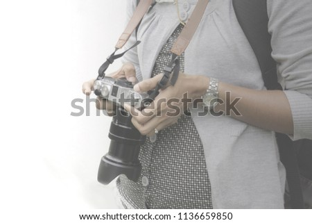 Close up woman photographer hand, wearing black tone dress and back pack, holding and checking picture from camera  long zoom lens with white cement wall background Vintage Travel and hobby concept #1136659850