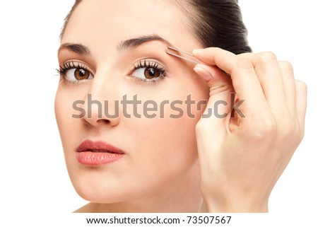 close up,  woman plucking her eyebrows with tweezers, isolated on white