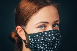 Close up woman portrait, Young woman wearing home made hygienic face medical mask to prevent infection, illness or flu and 2019-nCoV. Black background. Protection against disease, coronavirus.