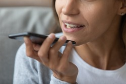 Close up woman recording voice message, speaking, young female holding phone in hand near face, chatting with friends online or speakerphone, activating digital assistant on smartphone