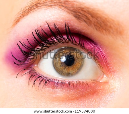 Close-up woman's beautiful brown eye with bright pink and violet makeup