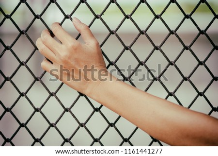close up woman's hand is caught on a metal fence. #1161441277