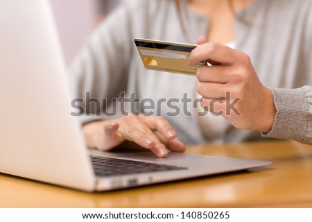 Close-up woman's hands holding a credit card and using computer keyboard for online shopping