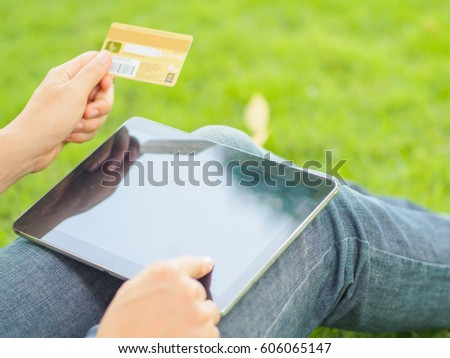 Close-up woman's hands holding a credit card and using tablet pc for online shopping #606065147