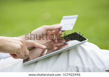 Close-up woman's hands holding a credit card and using tablet pc, online shopping, outdoor