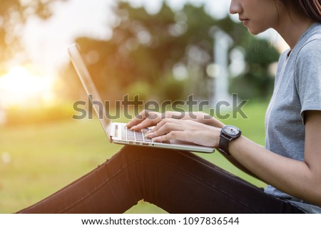 Close up woman sitting in the park at sunset time and using laptop computer