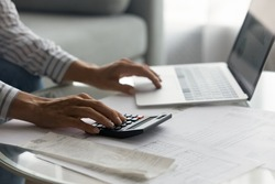 Close up woman using laptop and calculator, planning managing budget, businesswoman calculating bills, expenses, browsing online banking service, sitting at table with financial documents and receipt