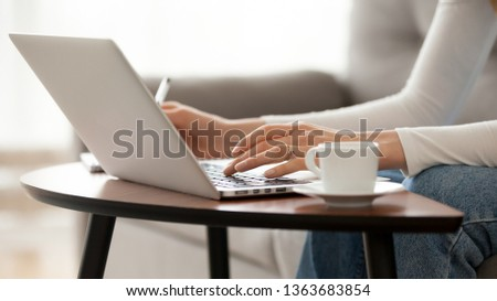 Close up woman using laptop, sitting on sofa, female hands typing, writing notes, studying languages, distance learning concept, checking email in morning, drink coffee, working at home