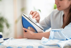 Close-up, woman wipes iron with soft cloth preparing to iron clothes on ironing board after washing at home Modern steam system, new household appliances. Caring for household appliances after work.