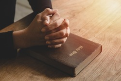 Close-up women christian read bible. Hands folded in prayer on a Holy Bible on wooden table.