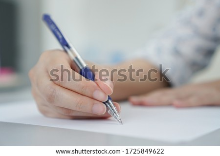 Close up women hand holding pen at paper.