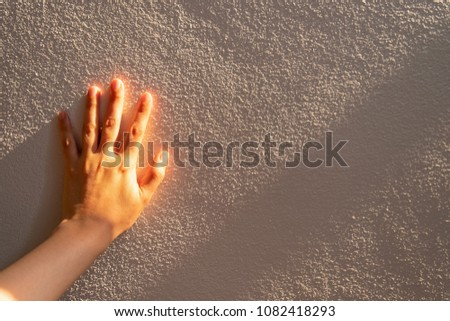 Close up women hand touches a white concrete wall with sunshine, shade and shadow in the morning. Copy space for text. #1082418293