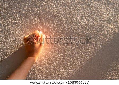 Close up women hand touches a white concrete wall with sunshine, shade and shadow in the morning. Copy space for text. #1083066287